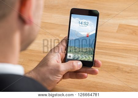 Businessman Holding Mobile Phone With Low Battery