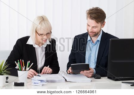 Two Businesspeople Calculating Bills