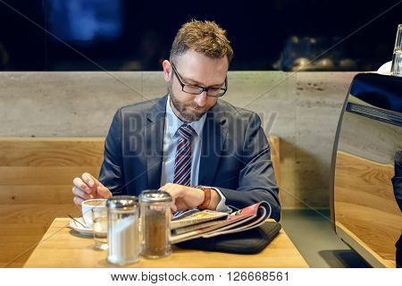 Handsome Businessman Sitting At Table With Coffee Reading