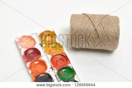 Close-up used watercolor paints and filament twine in coils isolated on white background. Art palette. Top view of the composition.