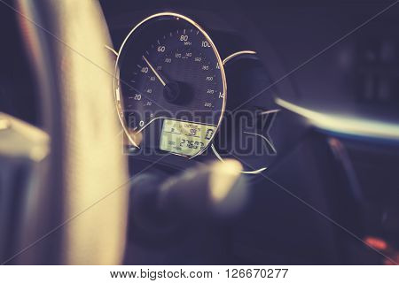 Vintage toned car dashboard with 99 degrees Fahrenheit temperature shallow depth of field.