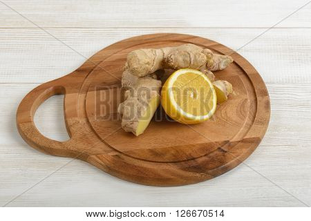 Combination of yellow lemon half and ginger laid out on a wooden cutting board . Ingredients to take for colds. Top view.