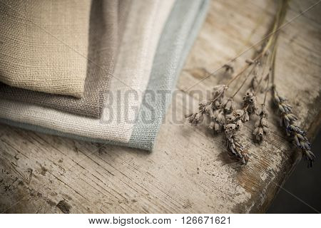 Stack Of Folded Linen By Edge Of Wooden Table