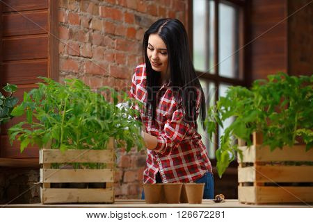 Her happy place. Portrait of a charming young female gardening indoors smiling to the camera cheerfully.