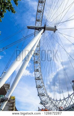 LONDON UK - JUNE 6 2015: Moving London Eye on blue sky background. London Eye is a giant Ferris wheel situated on the banks of the River Thames in London England United Kingdom