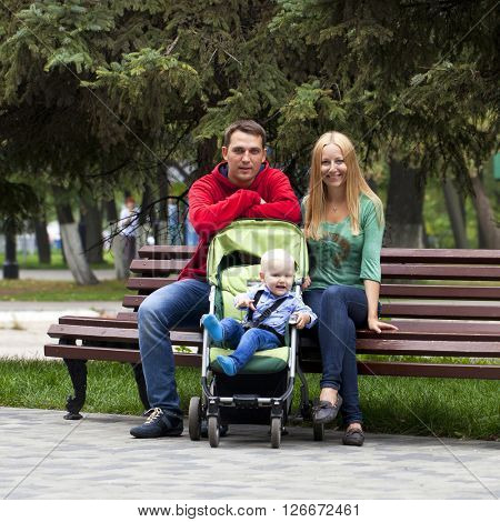 Young parents sit on a bench with his young son in summer park