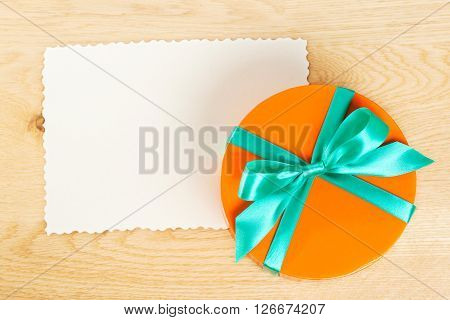 Orange gift box with blank gift tag on wooden background