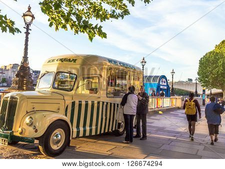 LONDON UK - JUNE 6 2015: Unidentified tourists are buying ice cream in an old automobile dealer at south bank of the River Thames promenade at the sunset time