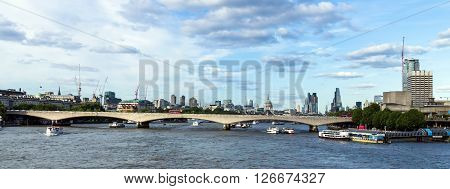 LONDON UK - JUNE 6 2015: City of London in late afternoon light from Hungerford Bridge. This view includes: St. Paul`s Cathedral The Leadenhall Building (The Cheesegrater) 20 Fenchurch Street (The Walkie-Talkie)Tower 42 and Waterloo Bridge.
