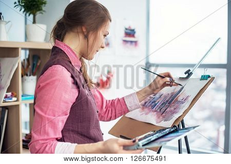 Side view portrait of a young woman painter drawing cityscape with watercolor palette on white paper using easel