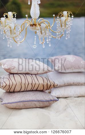 Still life details Cozy interior details soft and warm home decor. Colorful pillows on a sofa with little vase