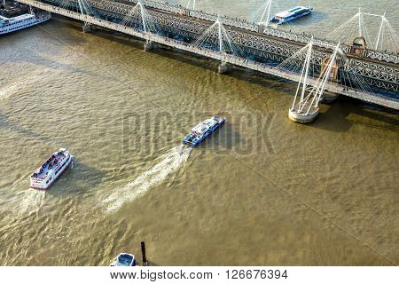 LONDON UK - JUNE 6 2015: Cityscape from London Eye with Haugerford Bridge over the Thames and tourist pleasure boats in late afternoon lite