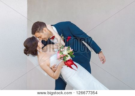 Young wedding couple enjoying romantic moments outside against gray background outdoors