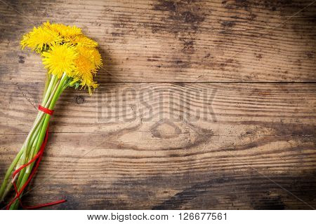Bouquet of dandelions with red ribbon on brown wood texture with empty space for text