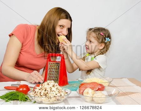 Six-year Girl With Pigtails Giving Mom A Bite Out Of A Piece Of Cheese At The Kitchen Table Where Th