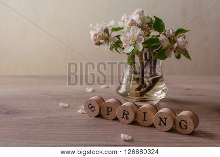 Fresh flowers in vase on wooden table spring concept