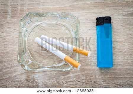 cigarettes in an ashtray with a lighter on a woody background