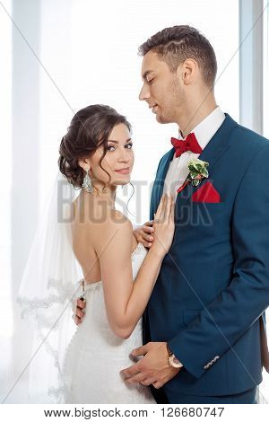 Young wedding couple enjoying romantic moments indoors against window