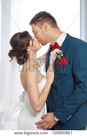Young wedding couple enjoying romantic moments kissing indoors against window