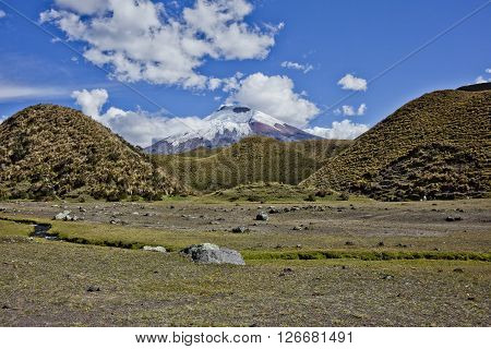 The volcano cotpaxi appears among the volcanic hills of the national park