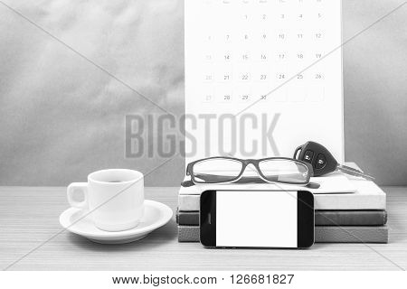 coffee and phone with car keyeyeglassesstack of bookcalendar on wood background black and white tone