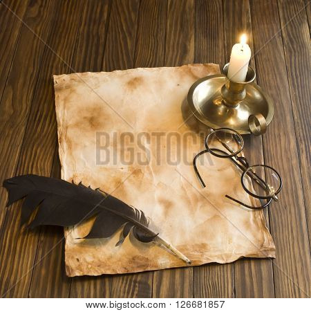Vintage letter concept. Candle, pen and glasses on the ancient wooden background