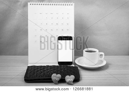 office desk : coffee with phonecalendarwalletheart on wood background black and white tone