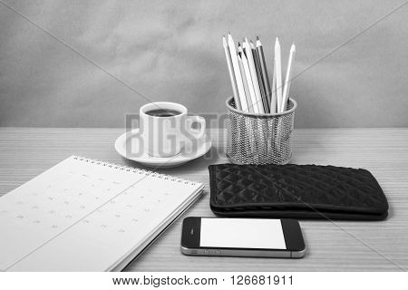 office desk : coffee with phonecalendarwalletcolor pencil on wood background black and white tone