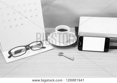 coffee and phone with keyeyeglassesstack of bookcalendar on wood background black and white tone