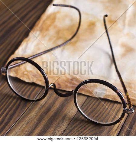 Old glasses on the vintage document in selective focus