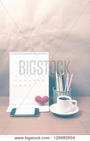 office desk : coffee with phone calendar heart on wood background vintage style