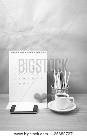 office desk : coffee with phone calendar heart on wood background black and white tone