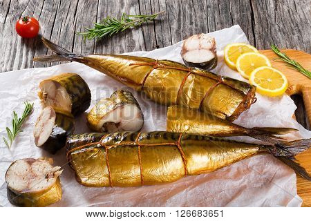 Slices of Smoked fish Mackerel or Scomber on a white parchment paper with cherry tomato sliced lemon and rosemary on an old wooden table studio ligths top view