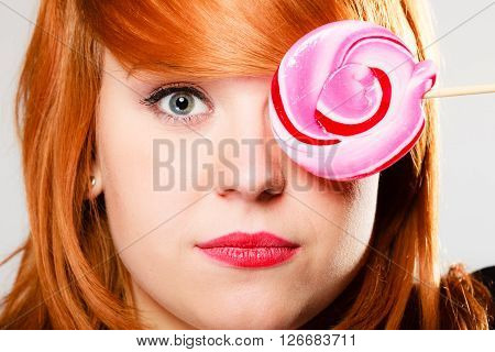 Closeup young woman holding candy. Redhair girl with pink lollipop covering her eye.