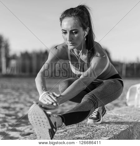 Fitness model athlete girl warm up stretching her hamstrings, leg and back. Young woman exercising with headphones listening music outdoors on beach or sports ground at evening summer.