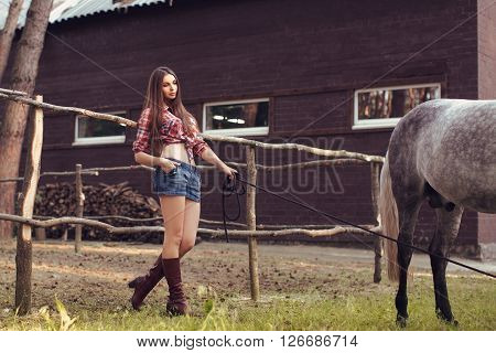 Portrait of young cowgirl and white horse outdoors near stable