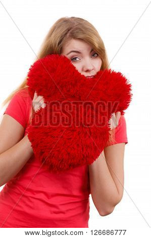 Woman blonde sad unhappy girl hugging red heart shaped big pillow studio shot on white. Heartbroken young female.