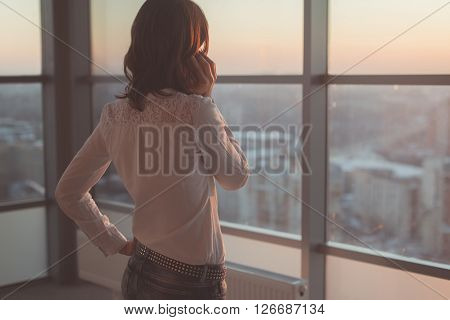 Rear view portrait of young worker speaking using cell phone, looking out the window. Female having business call, busy at her workplace in evening