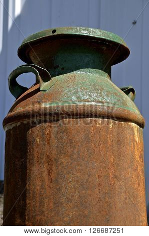 A rusty old ten gallon milk can once painted green displays a layer of rust and patina.