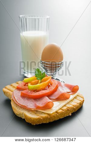 Fresh pork tenderloin sandwich with cheese tomato pepper and parsley arranged with boiled egg placed in a metal stand and glass of milk on neutral gray gradient background.