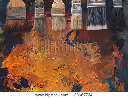 Paintbrush set lying on an old palette with oil paint brushstrokes top view photo