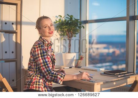 Side view of happy young woman working in home office, writing on paper. Female student learning material, doing task at workplace
