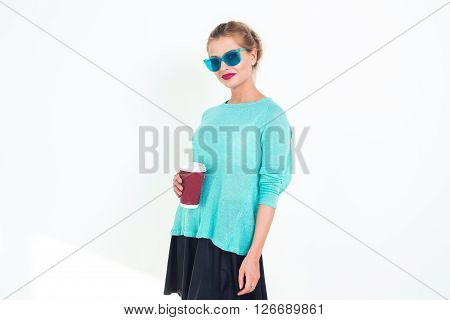 Woman wearing mint blue sunglasses and top with messy hairstyle, smiling. Portrait of fit blond glamorous female model posing, holding red coffee cup on white background, not isolated