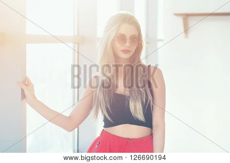 Close-up portrait of young beautiful woman wearing glamorous romantic summer look, with sunglasses in bright morning light, against large window