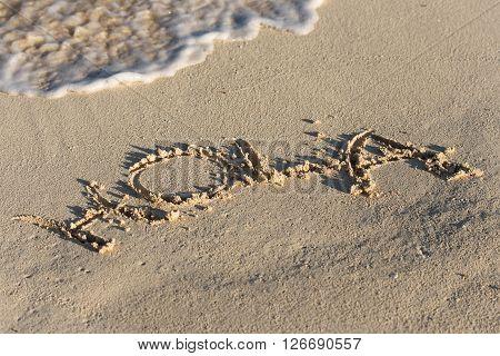 Inscription Hola On Sandy Beach With Wave's Foam