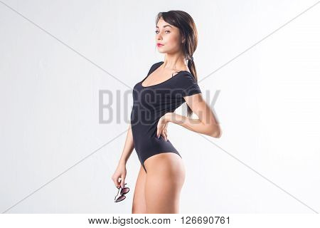 Young female model with perfect body and tail hairstyle standing sideways, putting her arm on hip, holding sunglasses, not isolated
