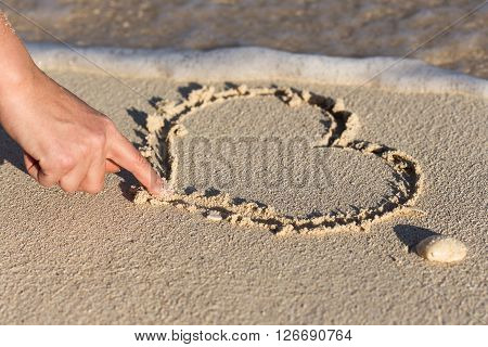 Female Hand Drawing Shape Of Heart On Sandy Beach