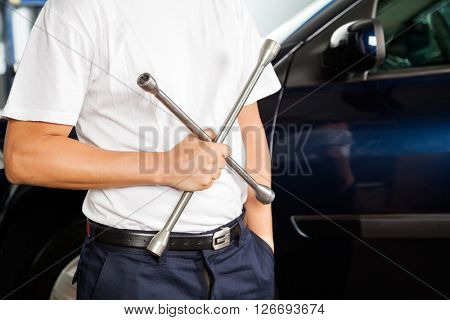 Midsection Of Mechanic Holding Rim Wrench