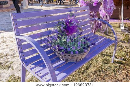 Wooden bench painted in purple and decorated with matching accessories.