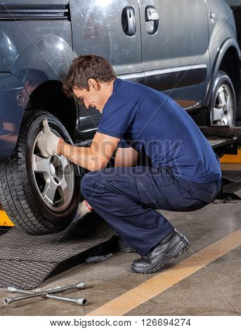 Mechanic Replacing Car Tire At Garage